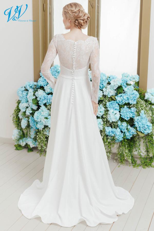 Hochzeitskleid mit langen Ärmeln. Das Kleid im klassischen Stil ist aus hochwertigem Krepp gefertigt. Das Hochzeitskleid im Bild hat Farbe ivory, dieses Kleid ist auch erhältlich in weiss.