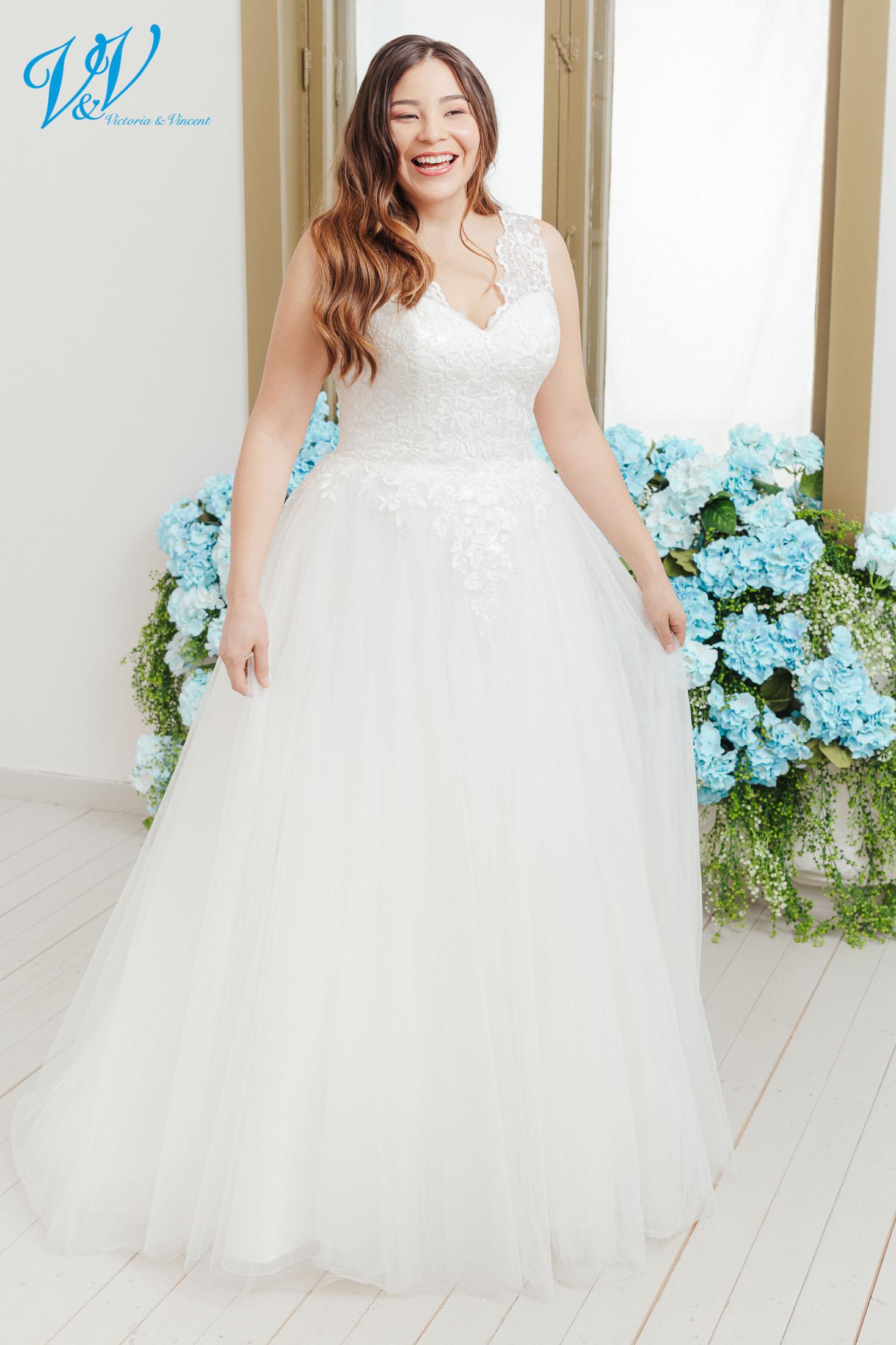 Plus Size Brautkleid. Romantisches große Größen Hochzeitskleid für kurvige Bräute. Breite Schulterriemen und der V-Ausschnitt vervollständigen den klassischen Look. Eingebaute Corsage für einen guten Sitz. Das Hochzeitskleid im Bild hat Farbe ivory, dieses Kleid ist auch erhältlich in weiss.